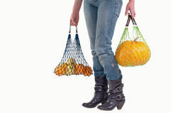 Woman holding string bags with yellow fruits. Woman with two shopping string bags (Einkaufsnetz) carrying yellow groceries (pumpkin, lemons, apples and oranges) Royalty Free Stock Photo