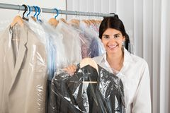 Woman holding suit in shop Stock Photos