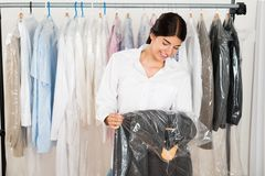 Woman holding suit in shop Royalty Free Stock Images