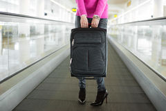 Woman holding suitcase in airport Stock Photo