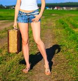 Woman holding suitcase Stock Images