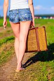 Woman holding suitcase on countryside road Stock Images