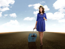 Woman Holding Suitcase Walking On The Road. Woman in blue dress and hat, walking alone in empty road Stock Images