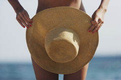 Woman holding summer hat in front of her tanned body. On the beach Royalty Free Stock Image