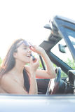 Woman holding sunglasses applying lipstick in convertible on sunny day Royalty Free Stock Photo