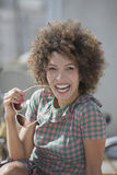 Woman holding sunglasses and laughing Royalty Free Stock Image