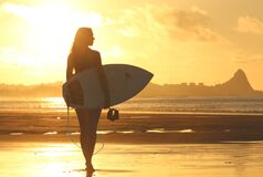 Woman Holding Surf Board Standing on Shoreline during Sunset Royalty Free Stock Image