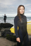 Woman Holding Surfboard With Male Surfer In Background. Portrait of confident young women holding surfboard with male surfer in background on beach Stock Photography