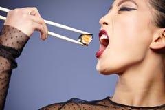 Woman holding sushi with chopsticks Stock Photo