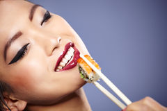 Woman holding sushi with chopsticks Royalty Free Stock Photos