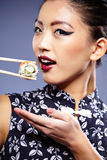 Woman holding sushi with chopsticks Stock Photos