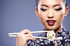 Woman holding sushi with chopsticks Stock Photography