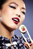 Woman holding sushi with chopsticks Stock Photo