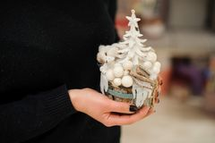 Woman holding a sweet Christmas composition made of white toy tree, bear and balls on the fir tree stump. Woman holding a sweet Christmas composition made of royalty free stock image