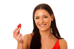 Woman holding sweet red strawberry in hand smiling isolated over Stock Images
