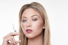 Woman holding syringe royalty free stock photos