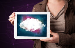 Woman holding tablet with cloud graphic. Casual young woman holding tablet with cloud concept and purple background Royalty Free Stock Image