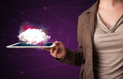 Woman holding tablet with cloud graphic. Casual young woman holding tablet with cloud concept and purple background Stock Photo