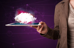 Woman holding tablet with cloud graphic. Casual young woman holding tablet with cloud concept and purple background Royalty Free Stock Photography