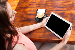 Woman holding tablet with coffee and smartphone aside stock image