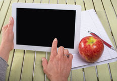 Woman holding a tablet computer with an apple Royalty Free Stock Photos