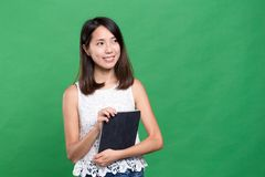 Woman holding tablet computer and looking far away. Asian young woman Royalty Free Stock Photo