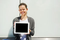 Woman holding a tablet computer over glass wall smiling over white wall Royalty Free Stock Image