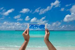 Woman holding tablet computer with screen on the tropical sea. t stock photography