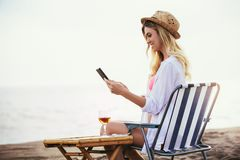 Woman holding tablet computer sitting on the beach royalty free stock photo