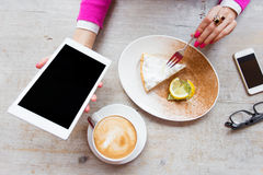 Woman holding tablet computer while sitting in cafe Stock Photos
