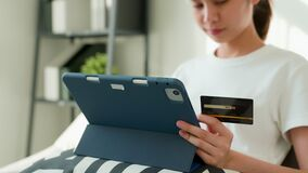 Woman holding tablet and credit card with paying for shopping online