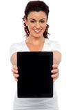 Woman holding tablet device, showing it to camera Stock Photo