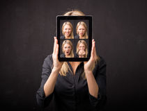 Woman holding tablet with different faces in front of her stock photography