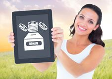 Woman holding tablet with donate box and money icon for charity. Digital composite of Woman holding tablet with donate box and money icon for charity royalty free stock photo