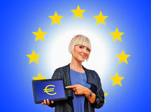 Woman holding tablet with euro money sign on european union bac Stock Photos