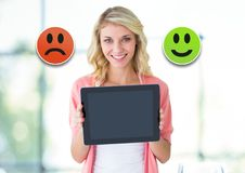 Woman holding tablet with feedback smiley face satisfaction icons. Digital composite of Woman holding tablet with feedback smiley face satisfaction icons royalty free stock image