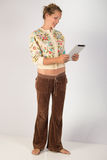 Woman Holding Tablet - Full Body Shot. A pretty young lady holding a tablet device. She could be using the tablet to interact with to communicate or play a game royalty free stock image