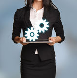 Woman is holding tablet with gears icon.  Stock Images