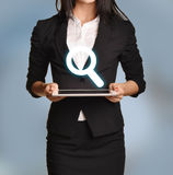 Woman is holding tablet with magnifier icon Stock Photography
