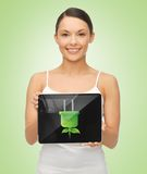 Woman holding tablet pc with green electrical plug Stock Photo