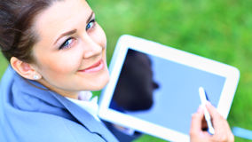 Woman holding tablet PC. On green grass lawn Royalty Free Stock Images