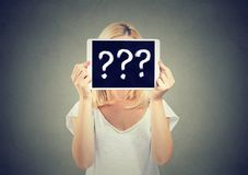 Woman holding tablet pc with question marks hiding her face Royalty Free Stock Images