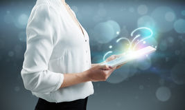 Woman holding tablet pc. And shiny magic comes from screen royalty free illustration