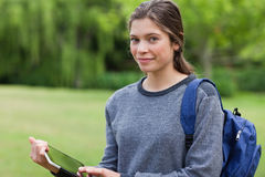 Woman holding a tablet pc while standing in a park Stock Photography