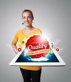 Woman holding tablet with red quality label Stock Image