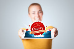 Woman holding tablet with red quality label in clouds Royalty Free Stock Photography