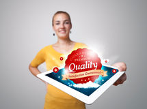 Woman holding tablet with red quality label in clouds Royalty Free Stock Image