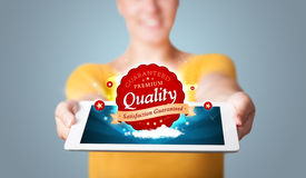 Woman holding tablet with red quality label in clouds Stock Photography