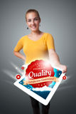 Woman holding tablet with red quality label in clouds Stock Photo