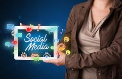 Woman holding tablet with social media graphics. Casual young woman holding tablet with social media icons Royalty Free Stock Photography